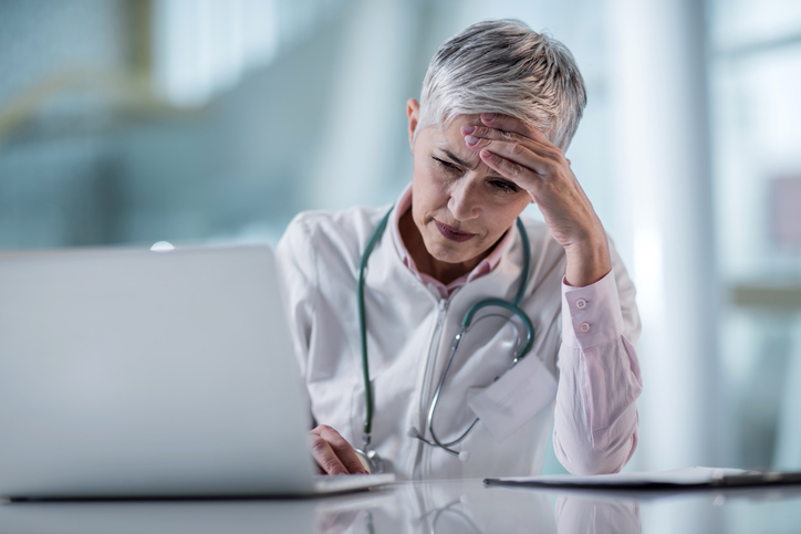 Female-physician-looking-at-laptop-and-stressed