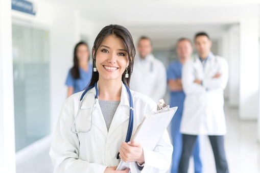 Smiling-female-physician-w-group-510412702